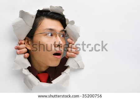 Man from hole in wall surprisingly looking away to his left side - stock photo