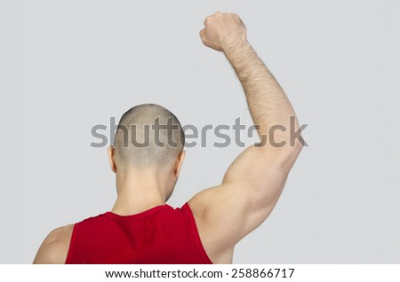 Man from the back raising his arm and fist. Fit bodybuilder with fist up in the air. Bald shaved man with muscles protesting. - stock photo