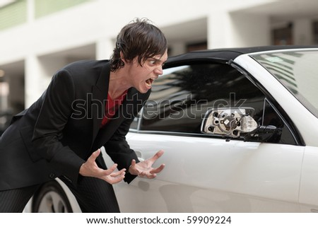 Man furious by the damage he discovers on his vehicle - stock photo
