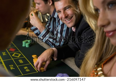 Man gambling at roulette table, smiling, portrait - stock photo