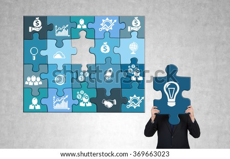 man gathering a blue business puzzle with business icons on each part. The man holding the last 'bulb' part missing so that he hides head behind it. Greyish background. Concept of doing business. - stock photo