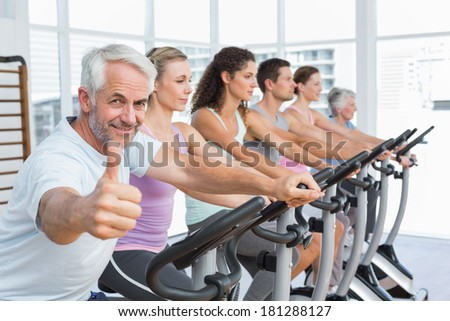 Man gesturing thumbs up with class working out at exercise bike class in gym - stock photo
