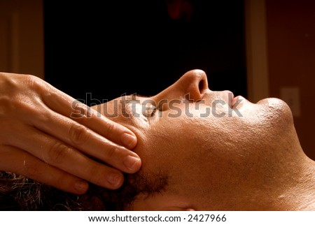 man getting a massage facial from therapist - stock photo