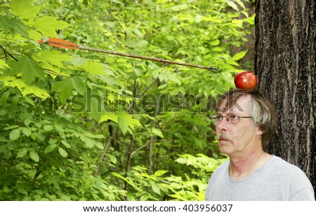Man getting an apple shot off his head showing trust as arrow is in mid air - stock photo
