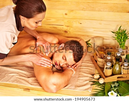 Man getting massage in bamboo spa. Female therapist. - stock photo