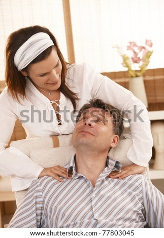 Man getting neck massage, looking up at masseur, smiling.? - stock photo