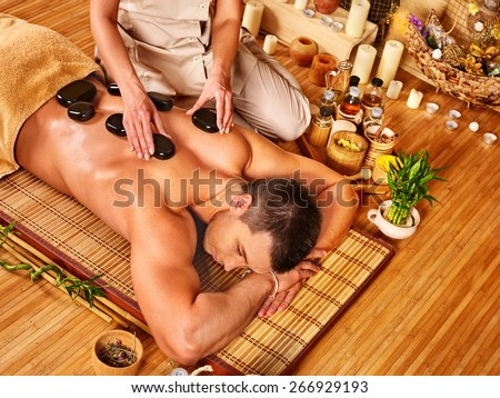 Man getting stone therapy massage in bamboo spa. Lying on floor. - stock photo