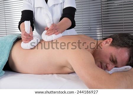 Man getting thai massage in the beauty salon - stock photo