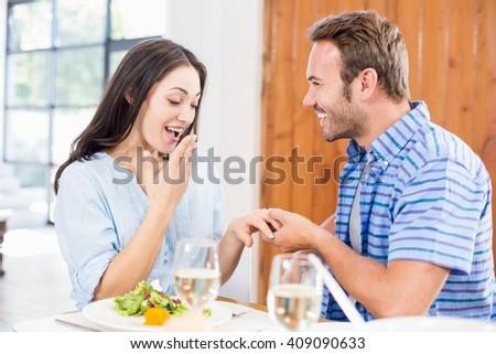 Man gifting finger ring to her woman at home - stock photo