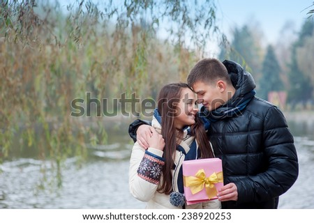 man gives his girlfriend a gift. - stock photo
