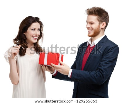 Man gives present wrapped in red paper to his girlfriend, isolated on white - stock photo
