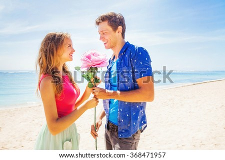 man giving a flower to a woman on a beach - stock photo