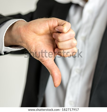 Man giving a thumbs down gesture of disapproval showing his negativity and dissatisfaction, close up of his hand. - stock photo