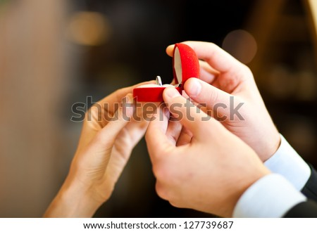 Man giving an engagement ring to his woman - stock photo