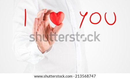 Man giving an inspirational message - I Love You - using a symbolic red heart shape held in his hand with handwritten text on white with copyspace for your message of love, affection or tenderness. - stock photo