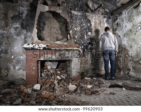Man giving back in ruins - stock photo