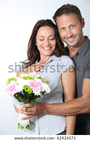 Man giving bunch of flowers to girlfriends - stock photo
