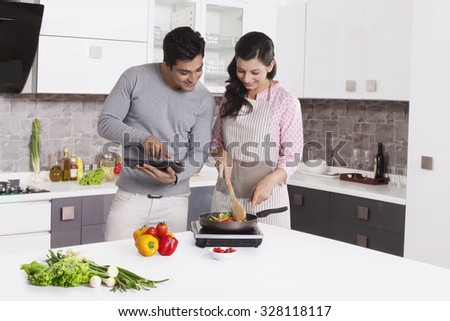 Man giving cooking tips from digital tablet - stock photo