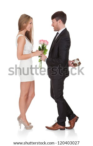 Man giving fresh flowers to woman. Isolated on white - stock photo