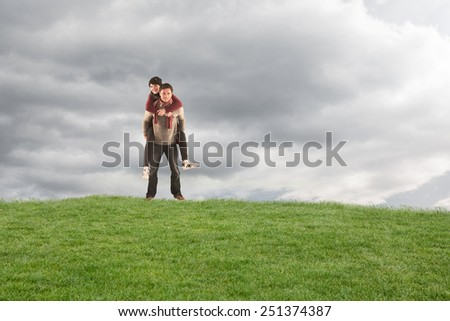Man giving girlfriend piggy back against cloudy sky - stock photo