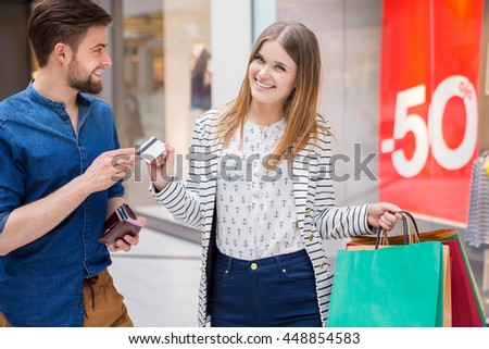 Man giving his girlfriend a credit card - stock photo