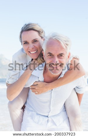 Man giving his smiling wife a piggy back at the beach on a sunny day - stock photo