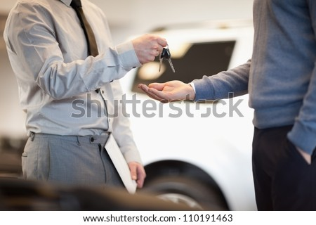 Man giving keys to another man in a car shop - stock photo