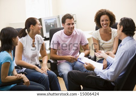 Man giving lecture to four people in computer room - stock photo