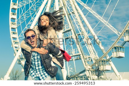 Man giving piggyback  - carrying on the back his girlfriend after a shopping day in the city. Picture of young joyful couple in front of ferris wheel - stock photo
