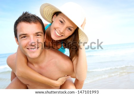 Man giving piggyback ride to girlfriend by the ocean - stock photo