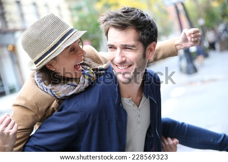 Man giving piggyback ride to girlfriend, having fun - stock photo