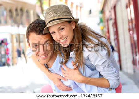Man giving piggyback ride to girlfriend in town - stock photo