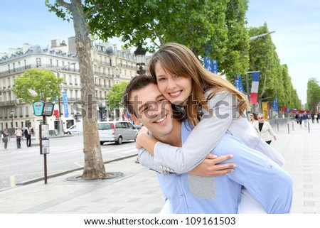 Man giving piggyback ride to girlfriend on the Champs Elysees - stock photo