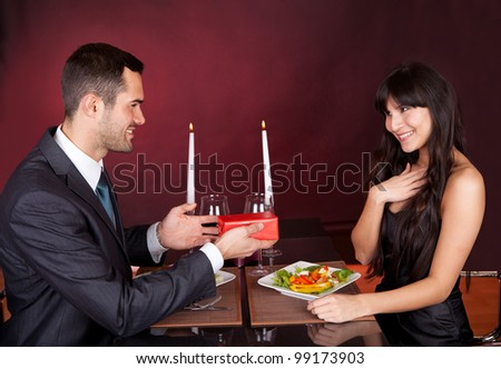 Man giving present to a woman at romantic dinner in restaurant - stock photo