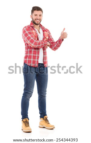 Man giving thumb up. Smiling young man in jeans and lumberjack shirt showing thumb up. Full length studio shot isolated on white. - stock photo