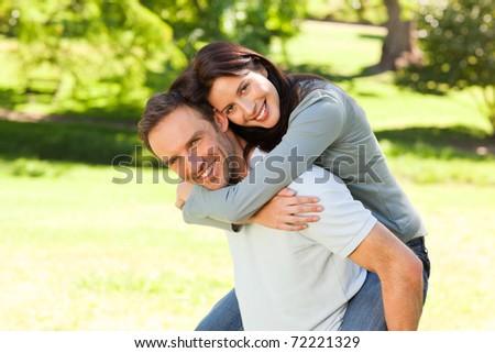 Man giving wife a piggyback - stock photo