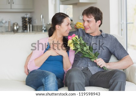 Man giving woman flowers on the couch - stock photo