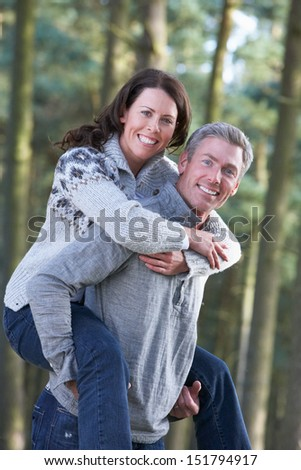 Man Giving Woman Piggyback On Country Walk - stock photo