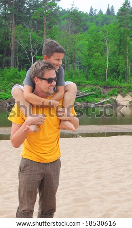 Man giving young boy piggyback ride outdoors smiling - stock photo