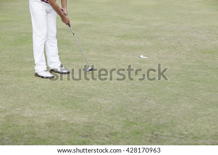 Man Golfer putt the golf ball into the hole for berdie - stock photo