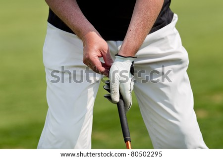 man golfs while wearing a blue polo and white trousers - stock photo