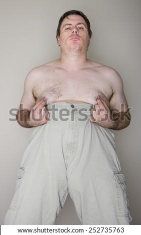 Man grabbing or pinching his nipples while holding his pants up - stock photo