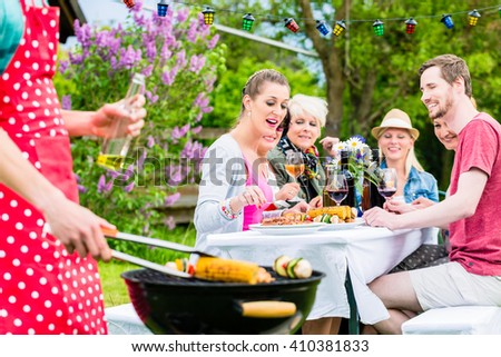 Man grilling meat and vegetables on garden party, his friends eating the bbq meat - stock photo