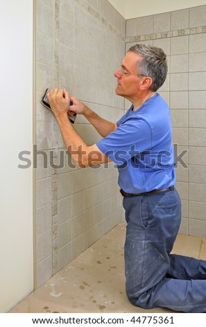 Man grouting ceramic tiles in bathroom - stock photo