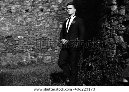 Man half face young handsome elegant model in suit with skinny necktie poses with hand in trouser pocket one leg backward outdoor black and white on masonry background - stock photo