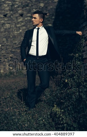 Man half face young handsome elegant model in unbutton suit with skinny necktie poses with hand in trouser pocket one leg backward holds arm sideward outdoor on masonry background - stock photo