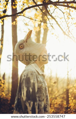 man half took off his rubber bird mask, standing in the autumn sunset forest thinking dramatically - stock photo