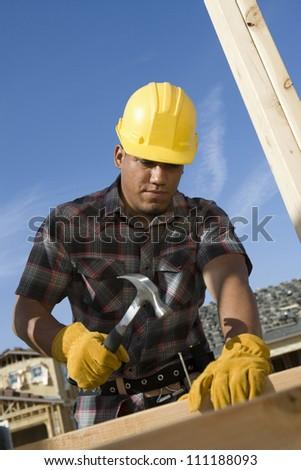 Man hammering nail to wooden beam - stock photo