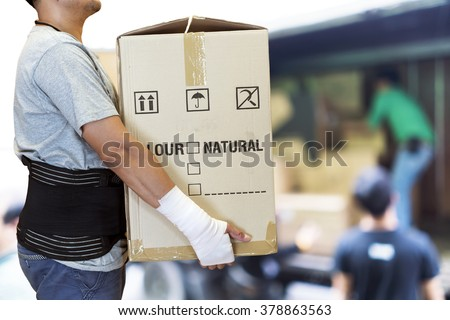 Man hand bandage, lift heavy carton wearing support belt for protect his back, blurred background of worker lift cartons  - stock photo