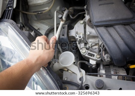man hand check and fill water in glass washer system Thailand Eco Car 1600cc with open hood show parts in side. - stock photo